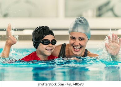 Cheerful boy with swimming instructor, learning to swim