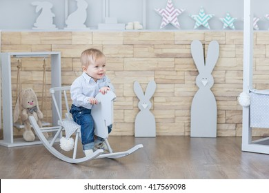 Cheerful boy Toddler baby swinging on a rocking chair in the shape of a horse.