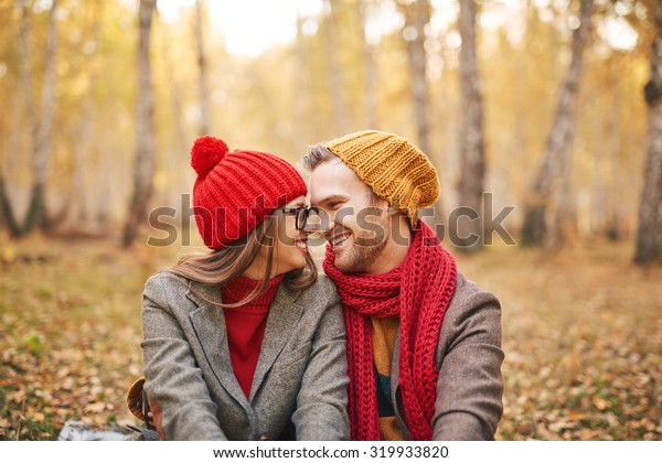Cheerful boyfriend and girlfriend looking at one another while relaxing outdoors