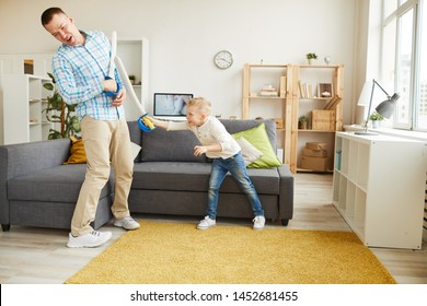 Cheerful brave little son hitting father with toy sword and winning father in sword-fighting game at home
