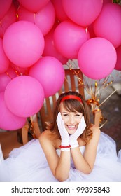 Cheerful bride of 60s style posing with bunch of balloons