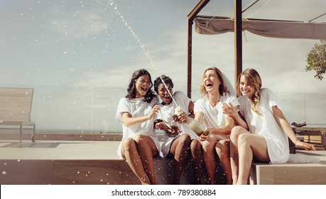 Cheerful bride and bridesmaids celebrating hen party with champagne while sitting on rooftop. Girls having a great time at the hen party.