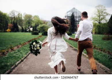 Cheerful bride and groom hold each other hands tender running across the street