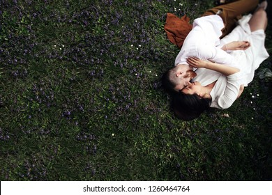 Cheerful bride and groom look happy lying on the green lawn covered with violet flowers