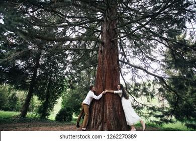 Cheerful bride and groom look happy posing before an old tree