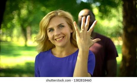 Cheerful bride showing engagement ring, groom standing on background, happiness