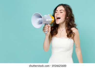 Cheerful bride young woman 20s in beautiful white wedding dress screaming in megaphone looking aside isolated on blue turquoise color background studio portrait. Ceremony celebration party concept