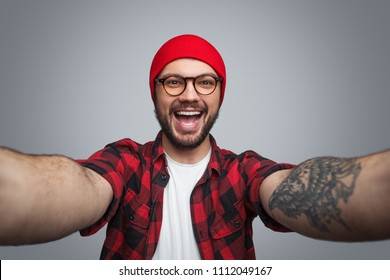 Cheerful bright bearded hipster in red and with tattoo on hand laughing at camera taking selfie on gray background
