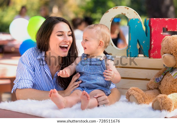 Cheerful bright colorful birthday celebration for beautiful baby boy with fun smiling mom