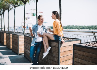 Cheerful bright man in casual wear talking to asian young lady crossing legs taking coffee drink and standing on promenade