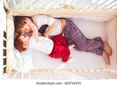 cheerful brothers having fun, lying in the crib together