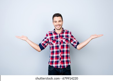 Cheerful brunet student in casual wear on pure background is gesturing with hands like he is holding something and need to choose between two options