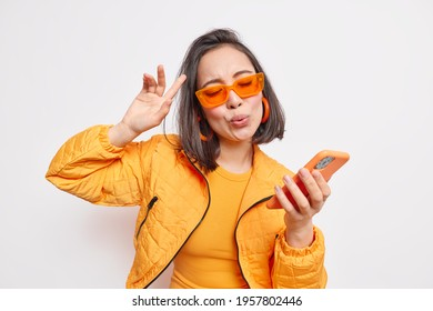Cheerful brunette Asian woman dance to favorite song moves to rhythm of music holds modern smartphone wears trendy orange sunglasses stylish jacket expresses happiness and joy models indoor.