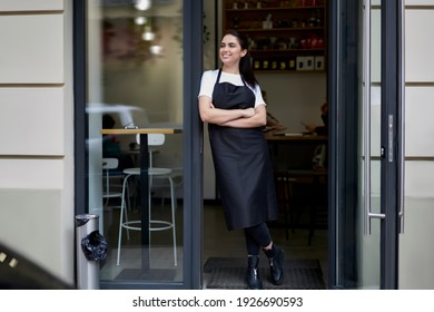 Cheerful brunette caucasian owner of coffee shop in apron standing at entrance greeting visitors and cliently hospitably, 20s smiling female barista in uniform opening cafeteria in morning