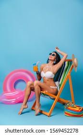Cheerful brunette girl enjoying summer. Studio shot of amazing slim woman sitting in chaise longue with juice.