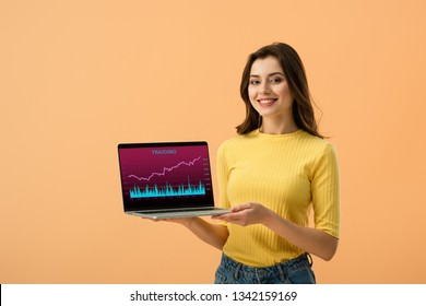 Cheerful brunette girl holding laptop with traiding website on screen isolated on orange