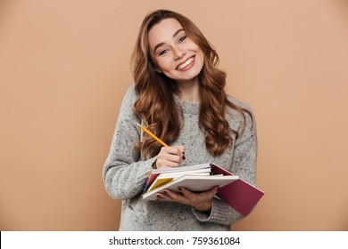 Cheerful brunette girl in knitted sweater writing notes on her sketchpad while looking at camera, isolated on beige background