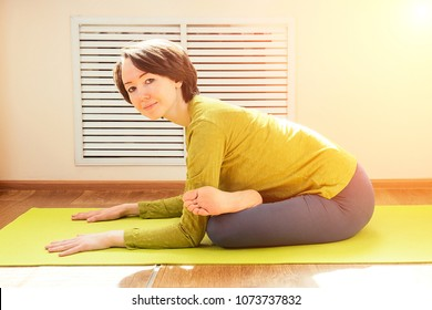 cheerful brunette woman in green blouse practicing yoga