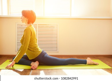 cheerful brunette woman in green blouse practicing yoga and doin