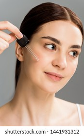 cheerful brunette woman holding pipette while applying serum on face isolated on grey