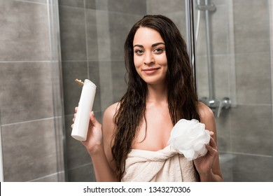 cheerful brunette woman holding shower gel and loofah in hands