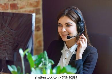 Cheerful brunette woman, kindly callcenter operator, wear black jacket and headphone set, sitting near computer pc before bricks wall loft background