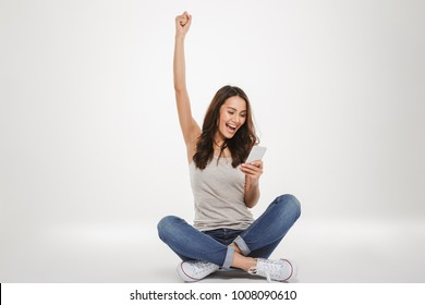 Cheerful brunette woman sitting on the floor and rejoices while using smartphone over gray background