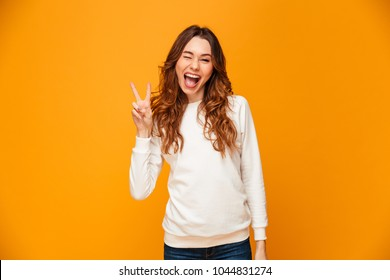 Cheerful brunette woman in sweater showing peace gesture and winks while looking at the camera over yellow background