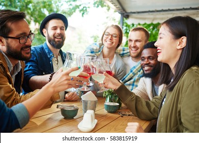 Cheerful buddies toasting with drinks