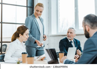 cheerful business coach standing near coworkers and gesturing near digital tablet