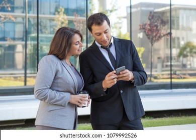 Cheerful business colleagues reading message on smarphone while resting outdoors. Smiling business people using mobile app in city park. Technology concept
