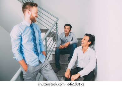 Cheerful business colleagues talking on stairwell