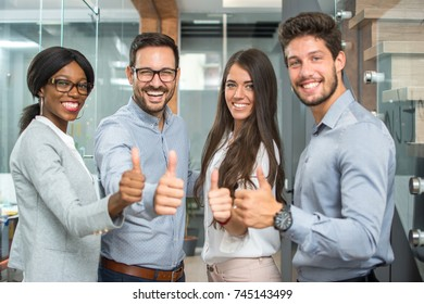 Cheerful business group showing thumbs up.