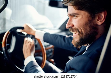Cheerful business man sits behind the wheel of a car and honks