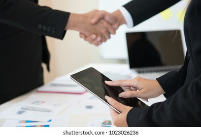 Cheerful business men shaking hands while business people applauding in the background,Successful business people shaking hands with business team clapping, successful and teamwork concept,