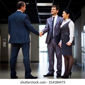 cheerful business men shaking hands