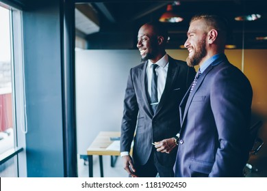 Cheerful business partners dressed in suits laughing looking at window in office during meeting, joyful male entrepreneurs happy about successful project planning for cooperation having fun together