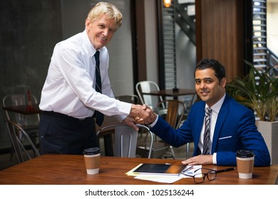 Cheerful business partners meeting in restaurant