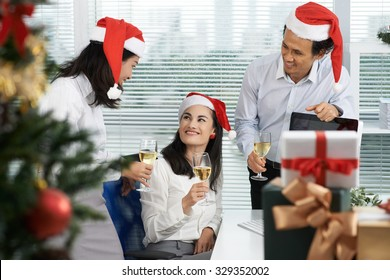 Cheerful business people celebrating Christmas in the office
