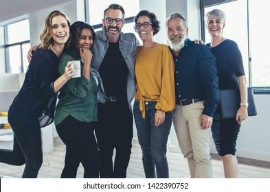 Des hommes d'affaires joyeux se rassemblent et rient. Une équipe de professionnels d'affaires regardant la caméra et souriant.