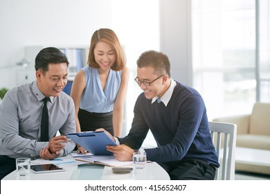 Cheerful business people working with documents together