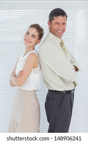 Cheerful business team posing back to back in bright office