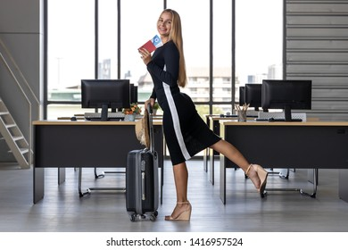 Cheerful business woman holding passport and luggage in workplace of office. Summer vacations concept.