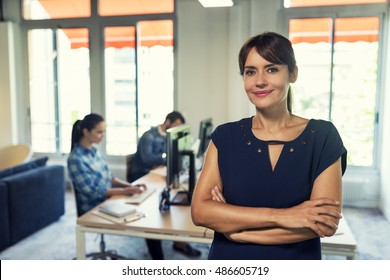Cheerful business woman manager in modern office space. Looking at camera. Staff in background.