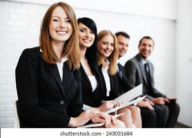 Cheerful business woman sitting wiht other professionals waiting for interview
