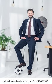 cheerful businessman akimbo standing with one leg on soccer ball in office