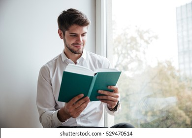 Cheerful businessman dressed in white shirt sitting in cafe and reading a book