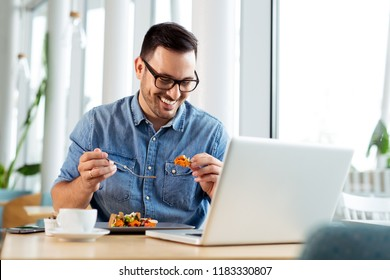 Cheerful businessman eating food in restaurant