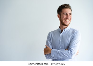 Cheerful businessman enjoying success. Young man in office shirt folding arms, looking away and smiling. Business success concept