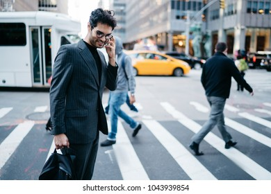 Cheerful businessman of financial company dressed in suit laughing during mobile conversation on smartphone while crossing zebra in metropolis.Positive successful lawyer talk on cellular in New York